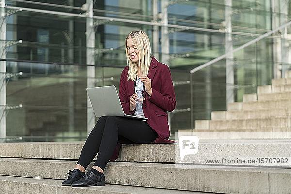 Blonde Geschäftsfrau benutzt Laptop und trinkt aus Wasserflasche  sitzt auf Stufen