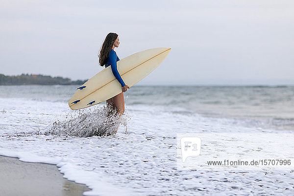 Young woman with surfboard at the beach  Kedungu beach  Bali  Indonesia
