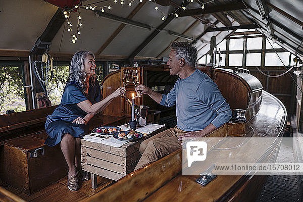 Senior couple having a candlelight dinner on a boat in boathouse clinking champagne glasses