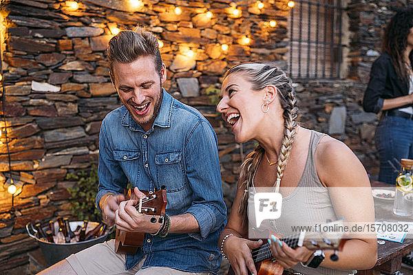 Glückliches Paar spielt in der Abenddämmerung Ukulele im Freien an einem Steinhaus