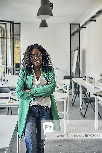 Portrait of a smiling businesswoman in office with colleagues in background