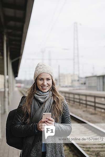 Portrait of smiling young woman with backpack and smartphone standing on platform