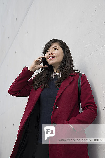 Portrait of modern businesswoman using smartphone in front of a wall