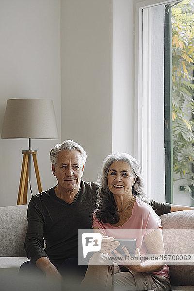 Porträt eines älteren Paares  das sich zu Hause auf der Couch entspannt