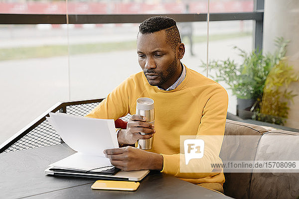 Man with reusable cup reading documents in a cafe