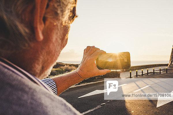 Älterer Mann benutzt ein Smartphone und macht ein Foto bei Sonnenuntergang  Teneriffa