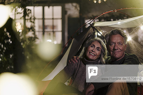 Happy senior couple camping in garden of their home at night