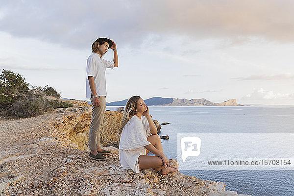 Junges Paar vor dem Meer mit Blick in die Ferne  Ibiza  Balearen  Spanien