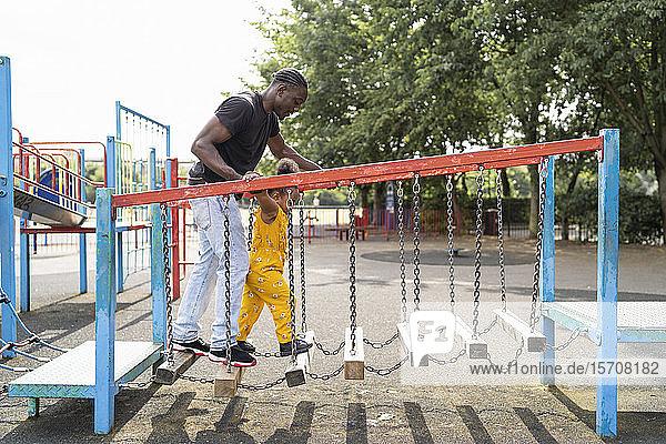 Vater und Tochter balancieren auf Holzstufen auf einem Spielplatz