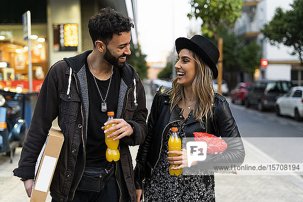 Laughing young couple with purchases in the city