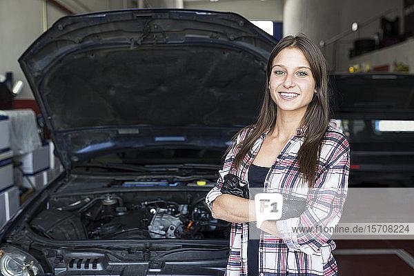 Lässige Frau mit kariertem Hemd und Handschuhen  die die Arme verschränkt hält und in die Kamera lächelt  arbeitet im Autoservice