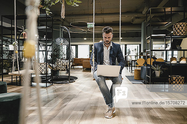 Businessman using laptop in coworking space  sitting on swing