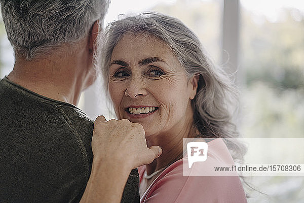 Portrait of smiling mature woman with her husband at home