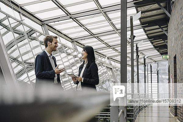 Lächelnder Geschäftsmann und Geschäftsfrau mit Tablettengespräch in modernem Bürogebäude