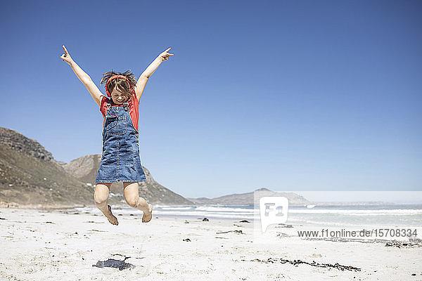 Mädchen hört Musik mit Kopfhörern am Strand  springt in die Luft  Kapstadt  Western Cape  Südafrika