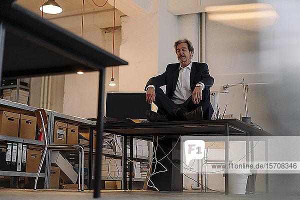 Senior businessman sitting cross-legged on desk in office meditating