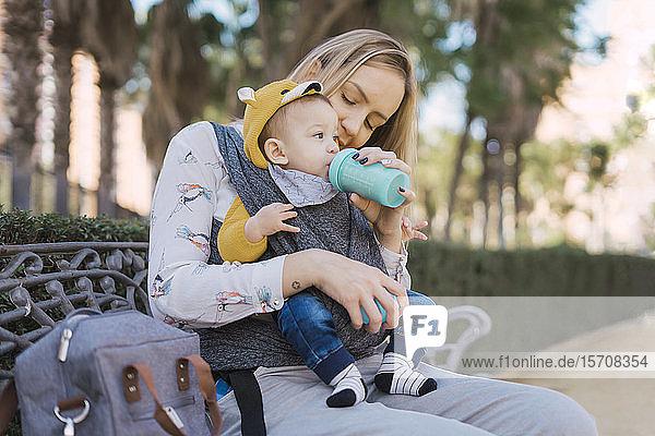 Mit der Flasche stillende Mutter eines Jungen auf einer Parkbank