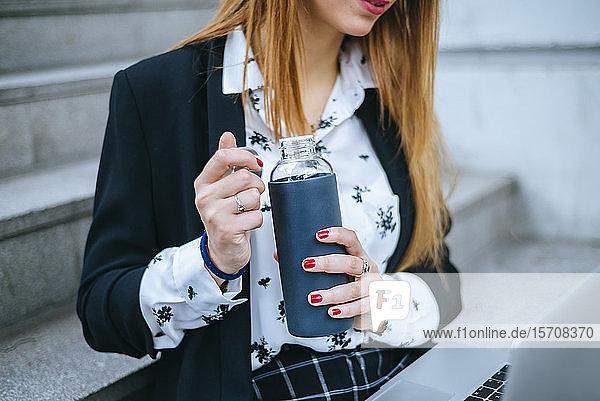 Nahaufnahme einer auf einer Treppe sitzenden Geschäftsfrau mit Laptop und wiederverwendbarer Flasche