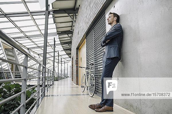 Geschäftsmann mit geschlossenen Augen an eine Wand gelehnt in einem modernen Bürogebäude
