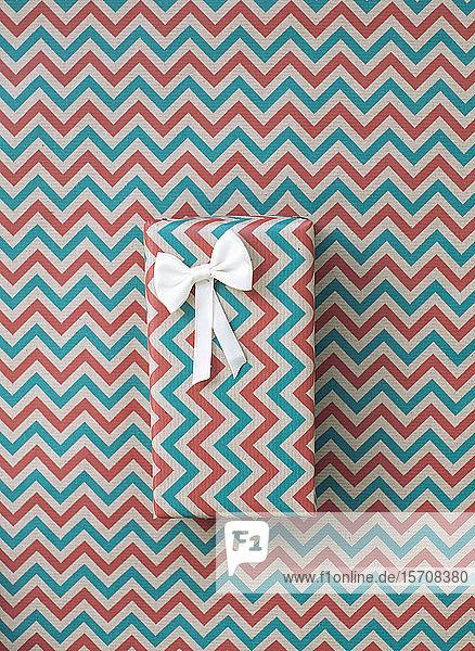 Weihnachtsgeschenk in Zick-Zack-Folie auf einem Hintergrund mit demselben Muster
