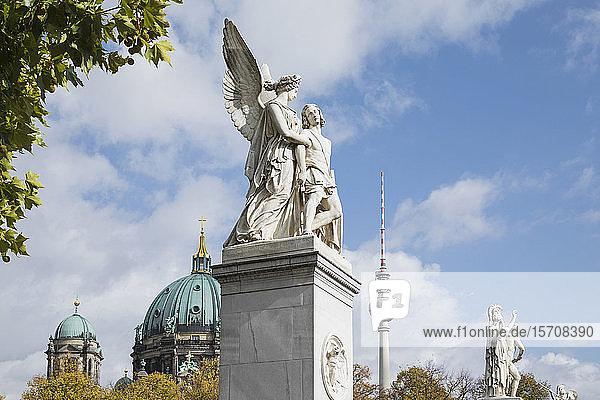 Germany  Berlin  Nike Assists Wounded Warrior statue with Berlin Cathedral and Berlin TV Tower in background