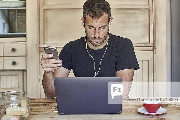 Mann arbeitet von zu Hause aus  sitzt am Küchentisch  benutzt Laptop und Smartphone