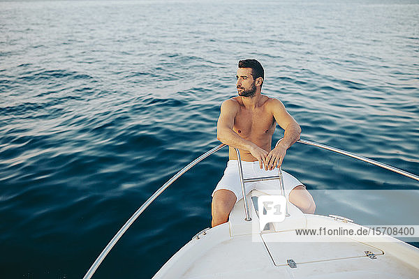 Young man sitting at bow of a boat  watching the sea