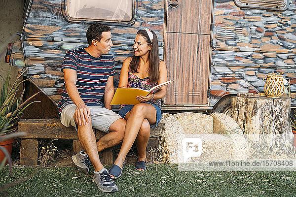 Mann und Frau mit einer Mappe sitzen an einem bemalten Wohnwagen