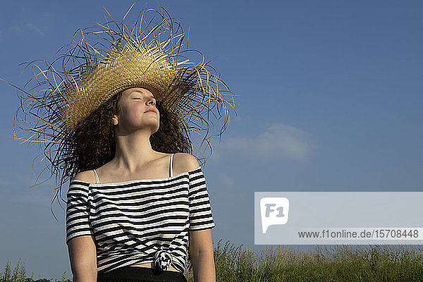 Portrait of young woman with eyes closed wearing frayed straw hat enjoying sunlight