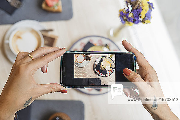 Draufsicht einer Frau in einem Cafe  die ein Handyfoto von Kaffee macht