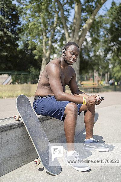 Skateboarder mit Smartphone im Skatepark Skateboarder mit Smartphone im Skatepark
