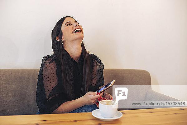 Junge Frau sitzt in einem Café  hält ein Smartphone in der Hand und lacht