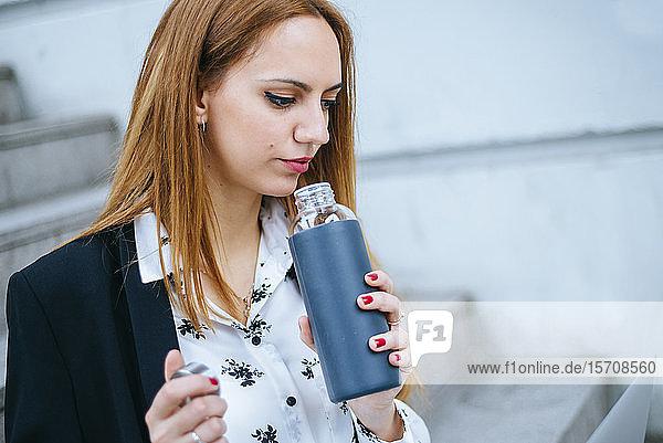 Junge Geschäftsfrau stößt im Freien auf wiederverwendbare Flasche