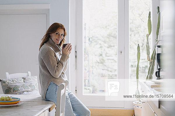 Woman drinking coffee in kitchen