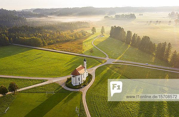 Deutschland  Bayern  Dietramszell  Luftaufnahme der ländlichen Felder und der Kirche St. Leonhard bei nebliger Morgendämmerung