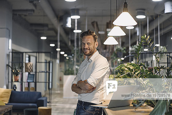 Portrait of smiling mature businessman with laptop in modern office lounge