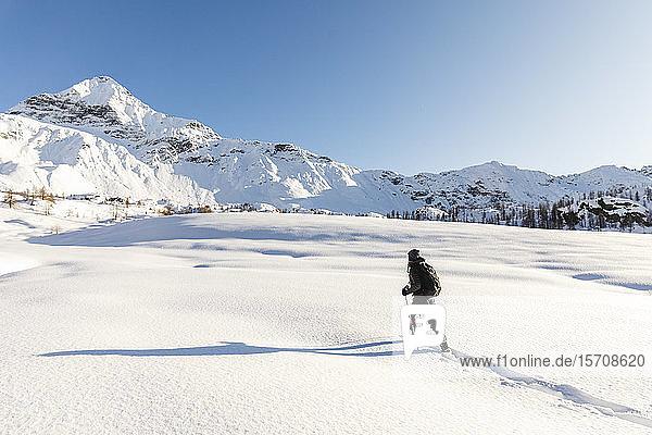 Frau wandert mit Schneeschuhen im Neuschnee in den Bergen  Valmalenco  Italien