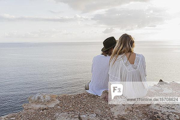 Rückenansicht eines jungen Paares  das auf einem Felsen vor dem Meer sitzt  Ibiza  Balearen  Spanien
