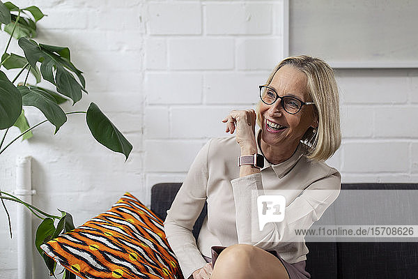 Happy mature businesswoman with smartwatch sitting on couch in office lounge