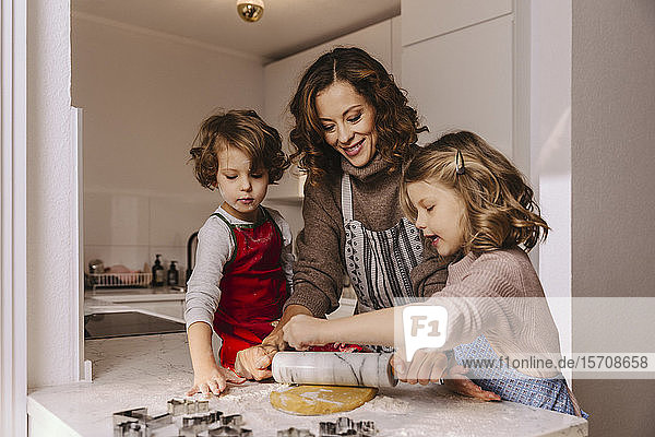 Mother and two daughters preparing Christmas cookies in kitchen