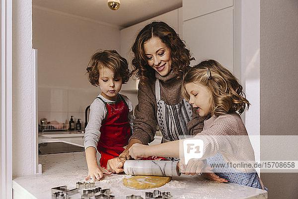 Mutter und zwei Töchter bereiten in der Küche Weihnachtsplätzchen zu