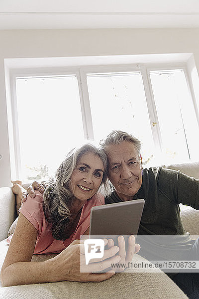 Portrait of happy senior couple relaxing on couch at home with tablet