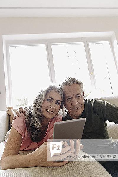 Porträt eines glücklichen älteren Paares  das sich zu Hause auf der Couch mit Tablette entspannt