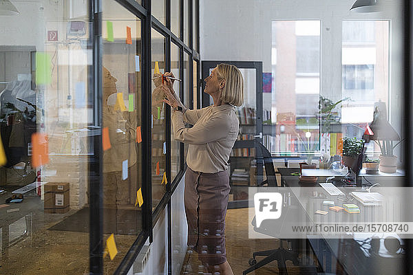 Mature businesswoman writing on adhesive notes on glass pane in office