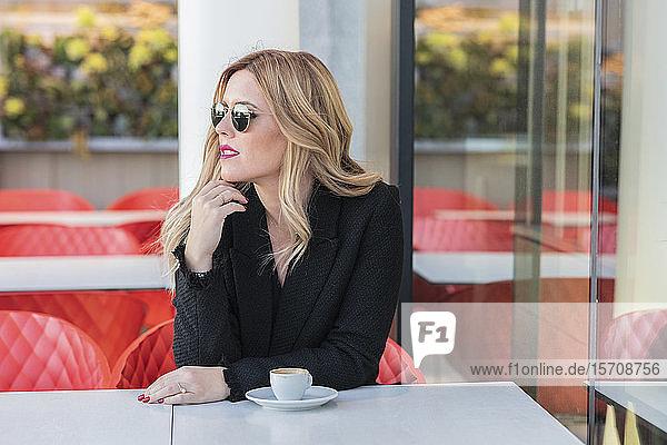 Geschäftsfrau mit Sonnenbrille nach der Arbeit mit einem Kaffee  seitwärts blickend
