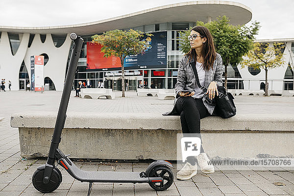Young businesswoman holding smartphone next to an e-scooter in the city