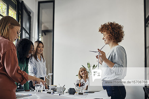 Businesswomen having a meeting in office with wind turbine models
