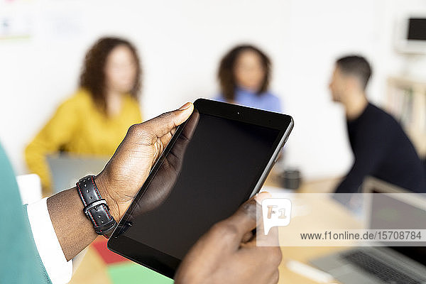 Nahaufnahme eines Geschäftsmannes im Büro mittels Tablett mit Kollegen im Hintergrund