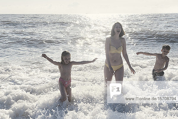 Happy mother with two kids having fun in the sea