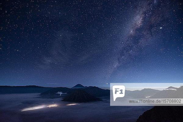 Indonesien  Ost-Java  Szenische Ansicht der Milchstraßen-Galaxie am sternenklaren Nachthimmel über dem nebelumhüllten Mount Bromo